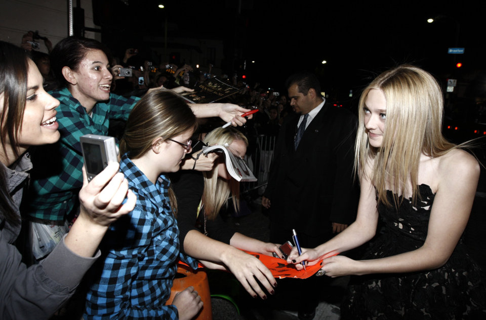 Photo - Actress Dakota Fanning signs autographs as she arrives at The Twilight Saga: New Moon premiere in Westwood, Calif. Monday, Nov. 16, 2009.  (AP Photo/Matt Sayles) ORG XMIT: CAGS130