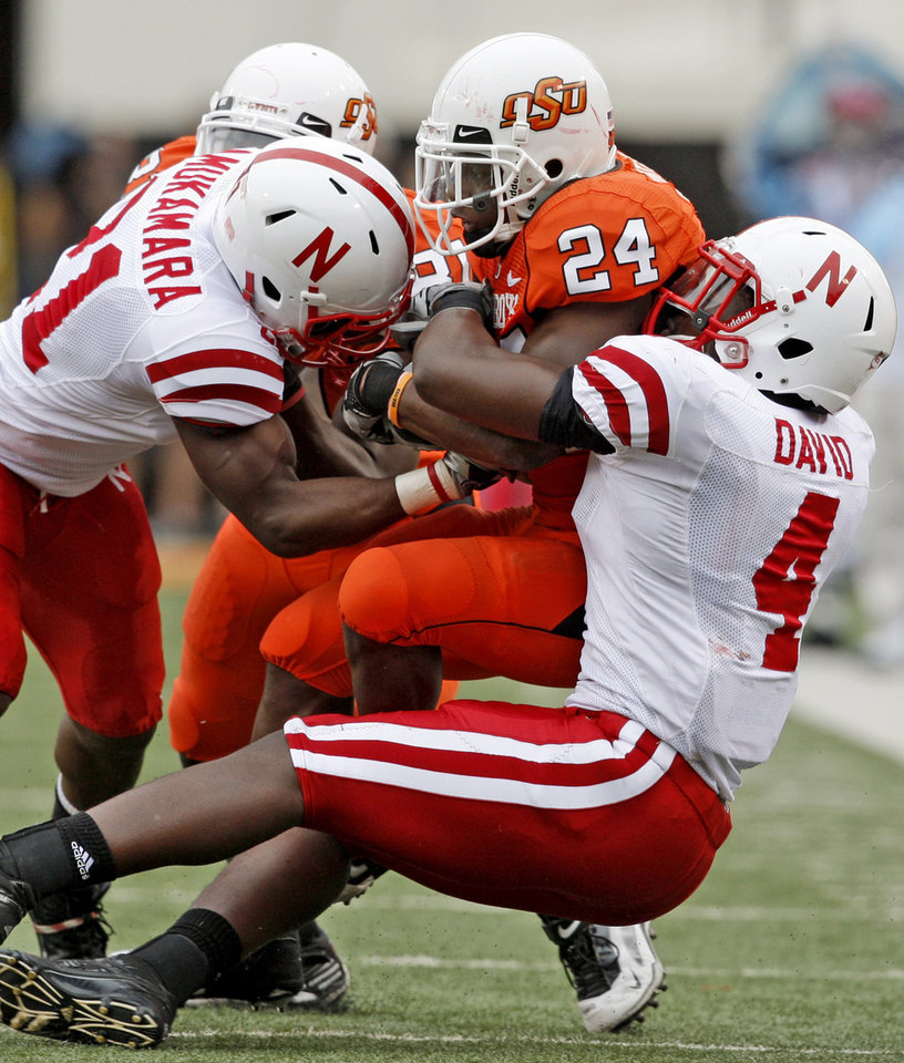 Photo - OSU's Kendall Hunter is brought down by Nebraska's Prince Amukamara, left, and Lavonte David during the college football game between the Oklahoma State Cowboys (OSU) and the Nebraska Huskers (NU) at Boone Pickens Stadium in Stillwater, Okla., Saturday, Oct. 23, 2010. Photo by Bryan Terry, The Oklahoman