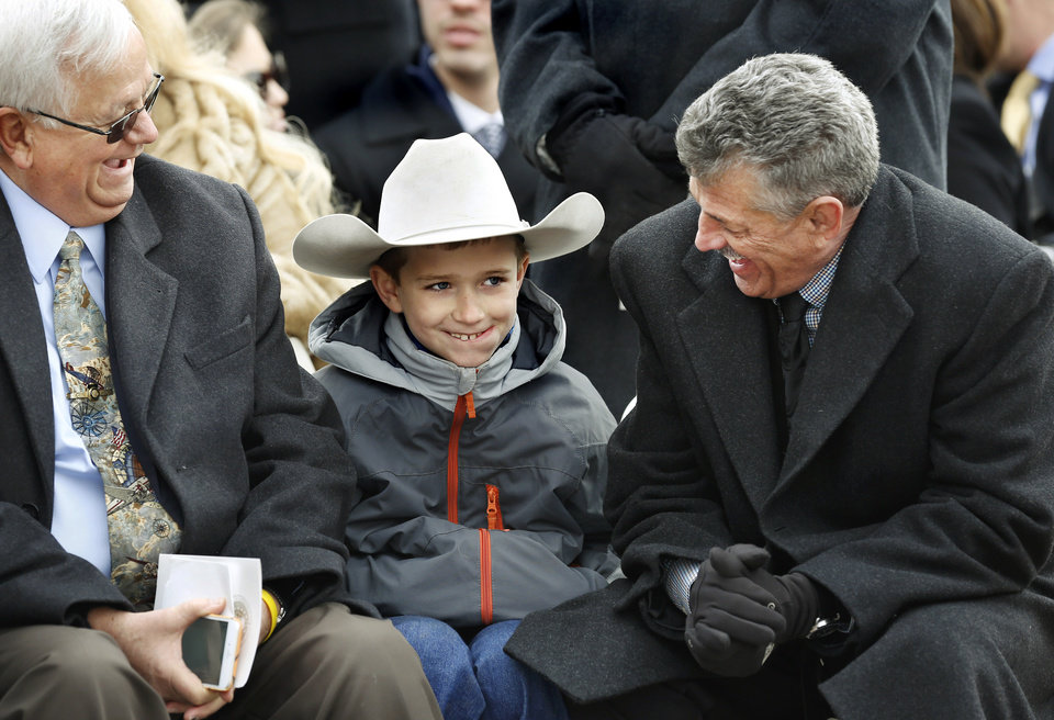 Photo - Stran Talley, 8, grins while sitting between his grandfather, Rep. John Talley, right, and retired Oklahoma Highway Patrol Trooper Stewart Meyer as they wait for  inauguration ceremony for Kevin Stitt to begin. The elder Talley is beginning his first term in the House of Representatives, serving District 33. Stran is a third grade student at Sangre Elementary School in Stillwater. It was the first time for both Talleys to attend an inauguration.  Stitt was sworn in as Oklahoma's 28th governor by Supreme Court Chief Justice Noma Gurich on Monday, Jan. 14, 2019. Photo by Jim Beckel, The Oklahoman.