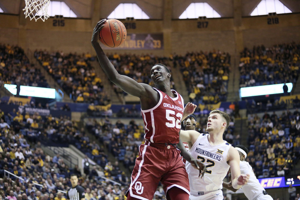 Photo - Oklahoma forward Kur Kuath (52) shoots the ball while defended by West Virginia guard Sean McNeil (22) during the first half of an NCAA college basketball game Saturday, Feb. 29, 2020, in Morgantown, W.Va. (AP Photo/Kathleen Batten)