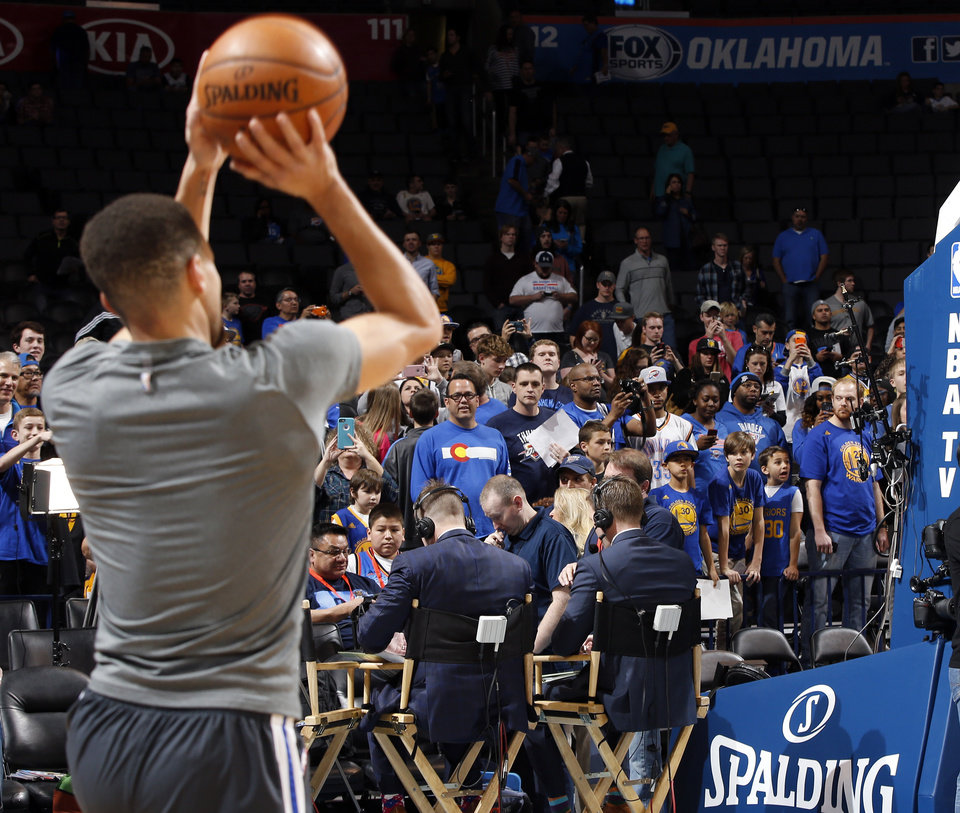 Photo - Fans watch the Golden State Warriors, including Stephen Curry (30), left, warm up before an NBA basketball game between the Oklahoma City Thunder and the Golden State Warriors at Chesapeake Energy Arena in Oklahoma City, Saturday, Feb. 27, 2016. Photo by Nate Billings, The Oklahoman
