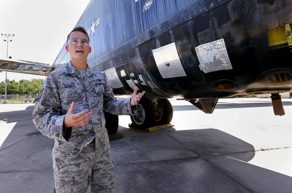 Photo -  Tech. Sgt. Kyle Schulz, with the 76th Expeditionary Depot Maintenance Flight, stands July 20 beside a bomber used for emergency temporary field repair training at the APL at Tinker Air Force Base. [Photo by Steve Sisney, The Oklahoman]