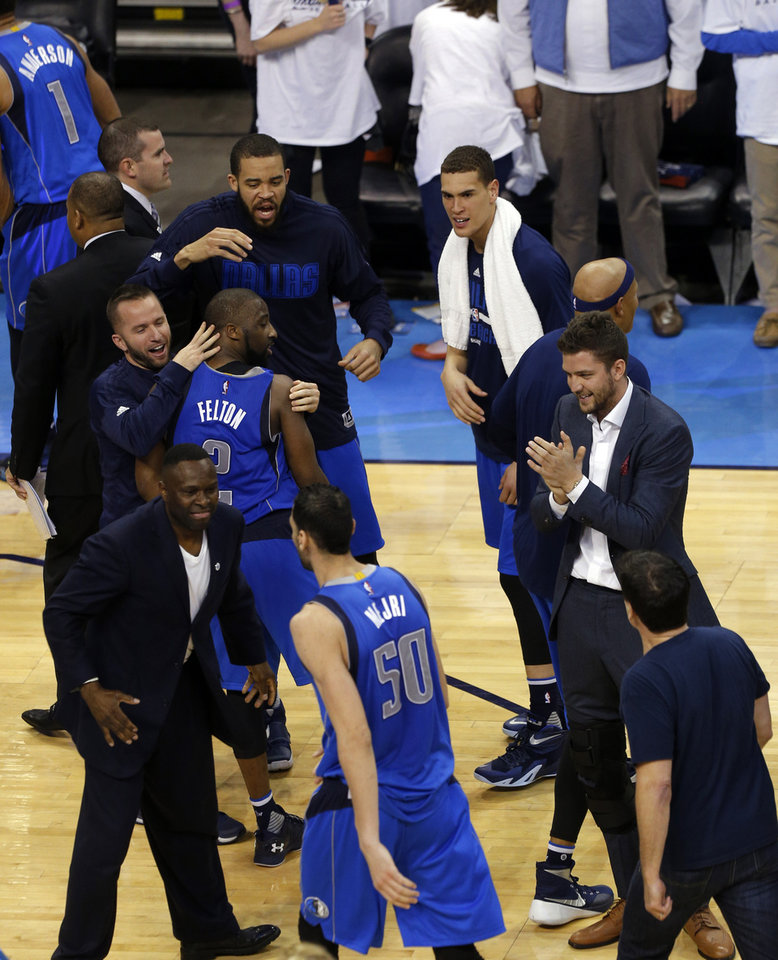 Photo - Dallas celebrates their win following Game 2 in the first round of the NBA playoffs between the Oklahoma City Thunder and the Dallas Mavericks at Chesapeake Energy Arena in Oklahoma City, Monday, April 18, 2016. Photo by Sarah Phipps, The Oklahoman