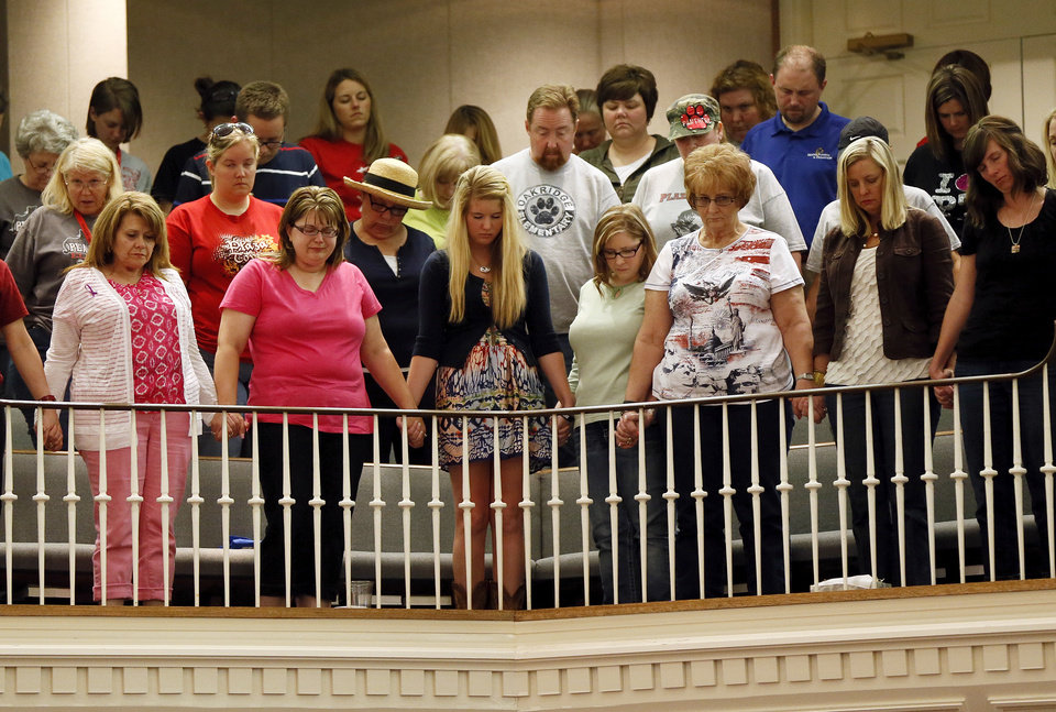 Photo - Moore educators, including some from Plaza Towers Elementary, stand and pray at the end of a district-wide meeting of Moore Public Schools employees at Southern Hills Baptist Church, 8601 Pennsylvania Ave., in Oklahoma City, Wednesday, May 22, 2013, after a tornado struck south Oklahoma City and Moore, Okla., on Monday. Photo by Nate Billings, The Oklahoman