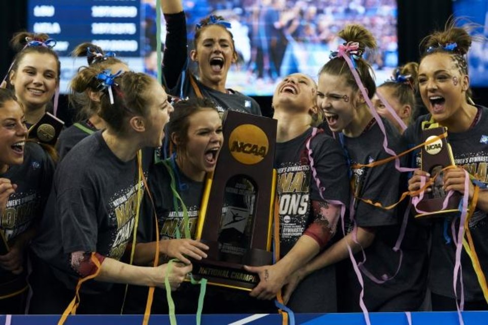 Photo -  Maggie Nichols, right, and the Sooners celebrate after winning the 2019 NCAA title in Fort Worth, Texas. [AP Photo/Cooper Neill]