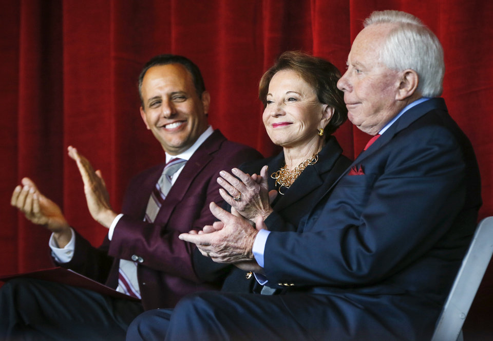 Photo - From left, Joseph Harroz Jr., interim president of the University of Oklahoma, Peggy Stephenson and Charles Stephenson applaud during the announcement of a $20 million gift from the Stephensons to the Stephenson Cancer Center, 800 NE 10 St., in Oklahoma City, Friday, Nov. 15, 2019. [Nate Billings/The Oklahoman]