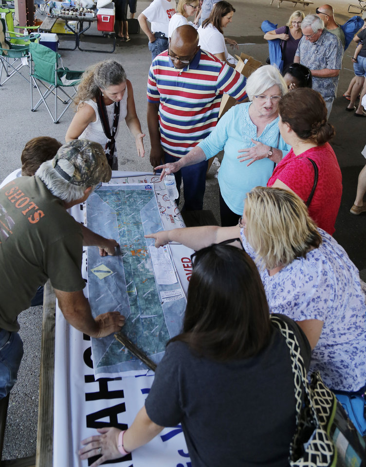 Photo - People gather around the map of the proposed route after the Victimsofiminentdomain.com rally at Choctaw Creek Park, in Choctaw, against the eastern Oklahoma county turnpike leg that the Oklahoma Turnpike Authority has proposed building Friday, August 12, 2016. Photo by Doug Hoke, The Oklahoman