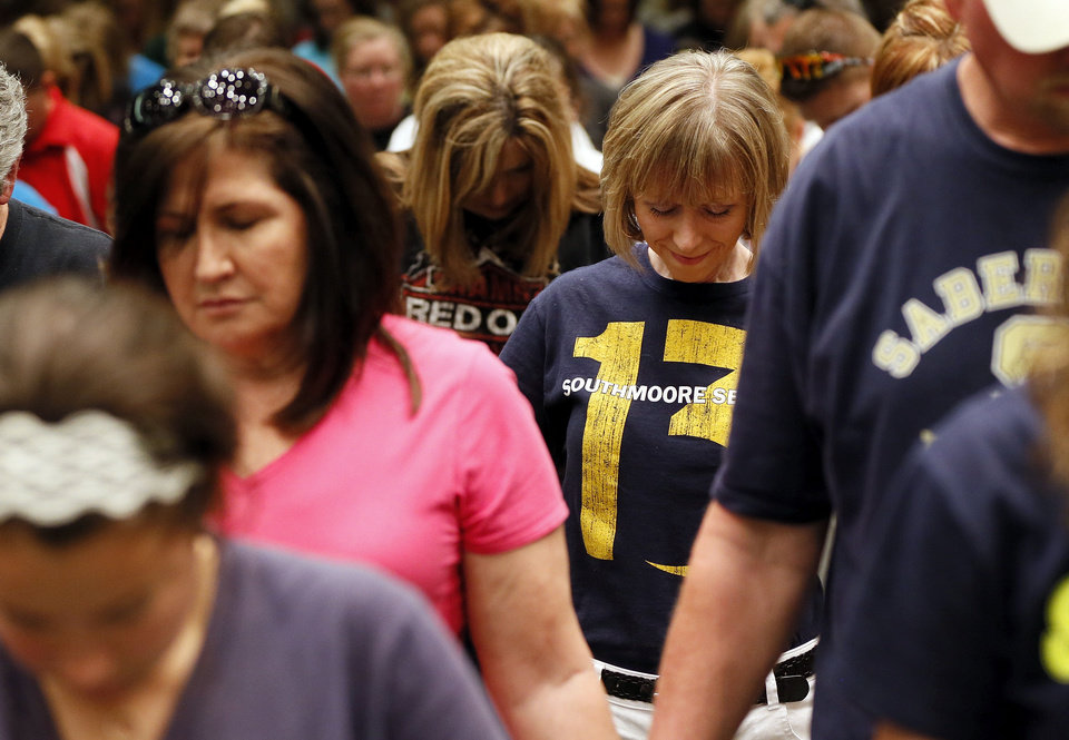 Photo - Employees of Southmoore High School pray together at the end of a Moore Public Schools staff meeting Wednesday afternoon at Southern Hills Baptist Church. Southmoore was the high school most affected by the storms that tore through town Monday afternoon. Superintendent Susan Pierce told employees to lean on one another through these difficult times. ?You have so many people in this family,? Pierce said.  NATE BILLINGS - THE OKLAHOMAN