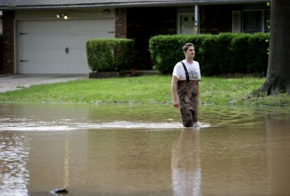 Photo - Grant Scepanski walks through his Indian Springs Estates neighborhood in Broken Arrow, Okla., as flood water from the Arkansas River rises Friday, May 24, 2019. (Mike Simons/Tulsa World via AP)