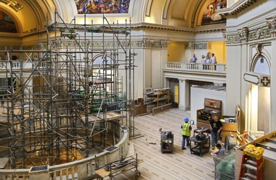 Photo -  This is the view showing work being done on the fourth floor rotunda of the Capitol on July 24. In the background, a family being given a tour of the building can be seen on a fifth floor balcony overlooking the rotunda. [Jim Beckel/The Oklahoman]