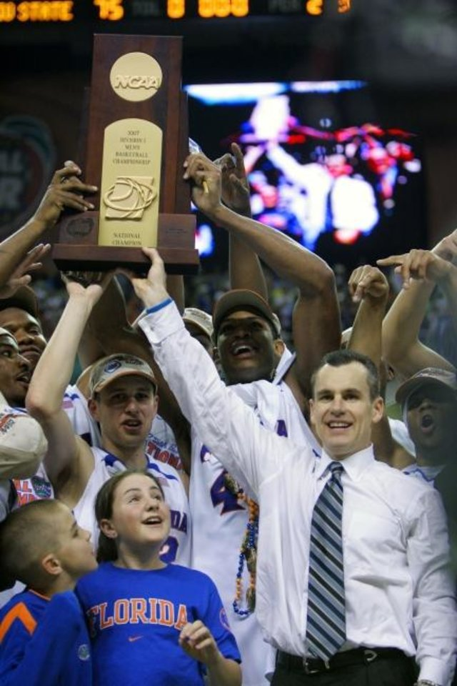 Photo -  Florida coach Billy Donovan, right, holds up the championship trophy after the Gators defeated Ohio State 84-75 in the 2007 NCAA final. [AP Photo/Gerry Broome, File]