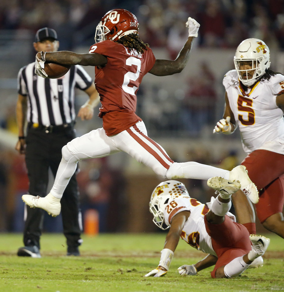 Photo - Oklahoma's CeeDee Lamb (2) leaps over Iowa State's Anthony Johnson (26) on his way to the end zone during an NCAA football game between the University of Oklahoma Sooners (OU) and the Iowa State University Cyclones at Gaylord Family-Oklahoma Memorial Stadium in Norman, Okla., Saturday, Nov. 9, 2019. [Bryan Terry/The Oklahoman]