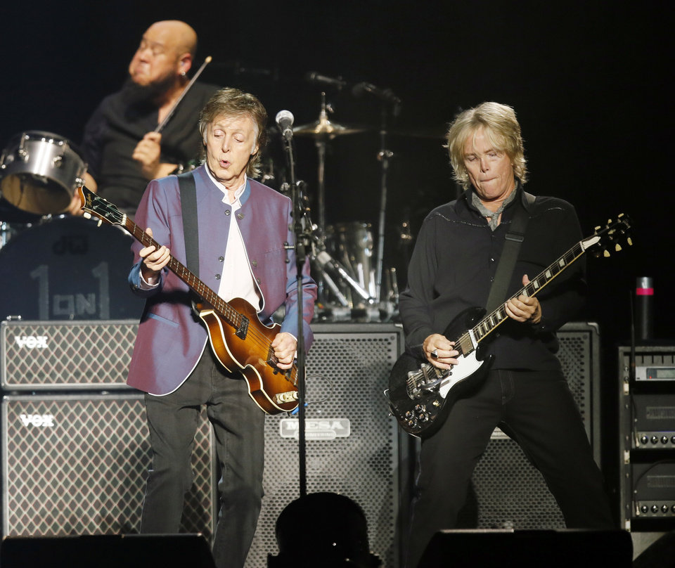 Photo -  Paul McCartney, left, performs with guitarist Brian Ray during McCartney's