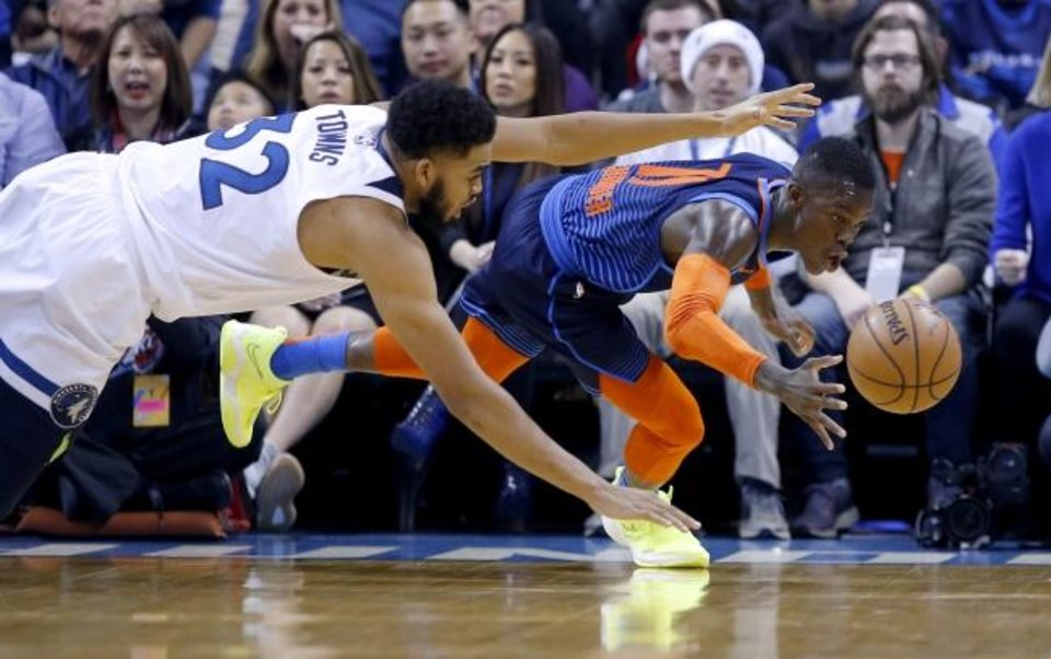 Photo -  Oklahoma City's Dennis Schroder (17) and Minnesota's Karl-Anthony Towns (32) dive for a loose ball last season at Chesapeake Energy Arena. [Sarah Phipps/The Oklahoman]