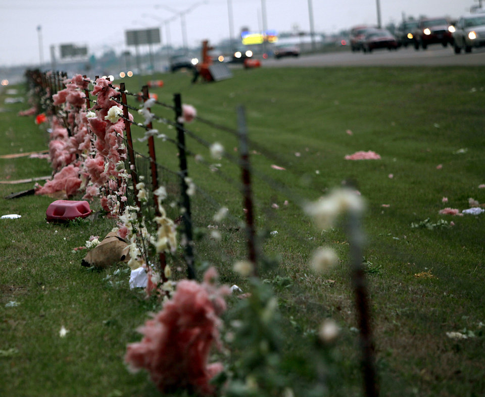 Photo - Southbound traffic passes debris blown into a fence during a storm on I-35 near  Hillsdale Free Will Baptist College in Norman on Monday, May 10, 2010. By John Clanton, The Oklahoman