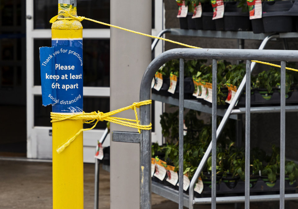 Photo - Signs remind customers to stay six feet apart for social distancing to help combat the coronavirus at the Walmart location in Yukon, Okla. on Monday, April 13, 2020.  [Chris Landsberger/The Oklahoman]