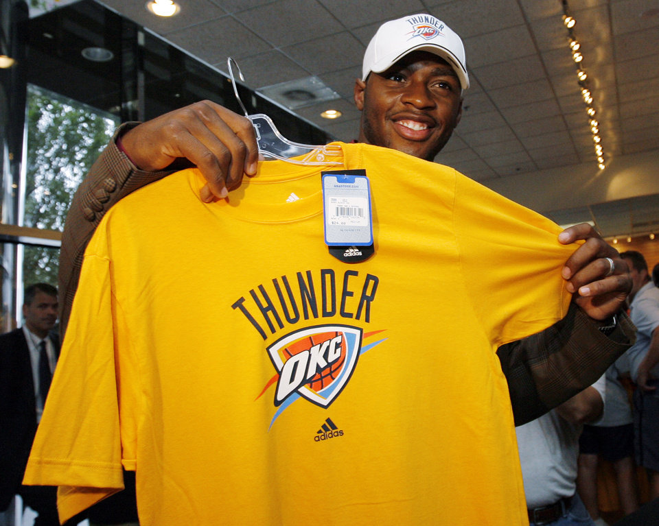 Photo - OKC Thunder player Desmond Mason poses with a shirt and hat in the team store after the unveiling of the Oklahoma City Thunder NBA team name at Leadership Square in downtown Oklahoma City, Wednesday, September 3, 2008. NATE BILLINGS, THE OKLAHOMAN
