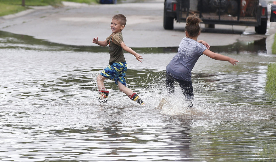Photo - Kayden Evans, left, 6, and Keely Younger, 6, play in the water on a flooded street in El Reno, Okla., following heavy rains Tuesday, May 21, 2019. (AP Photo/Sue Ogrocki)