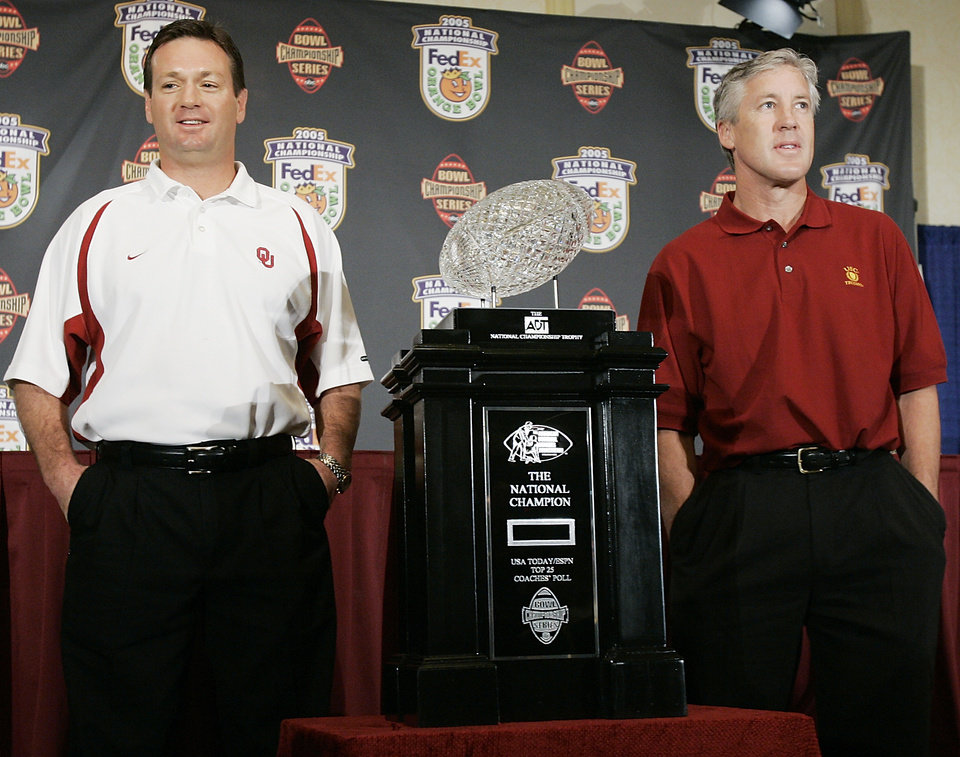 Photo - MIAMI, FL, MONDAY, JANUARY 3, 2004.    University of Oklahoma (OU) college football coach Bob Stoops and University of Southern California (USC) coach Pete Carroll pose with the National Championship trophy the day before the Orange Bowl. OU plays #1 USC January 4 in the Orange Bowl in Miami. Oklahoman photo by Ty Russell.
