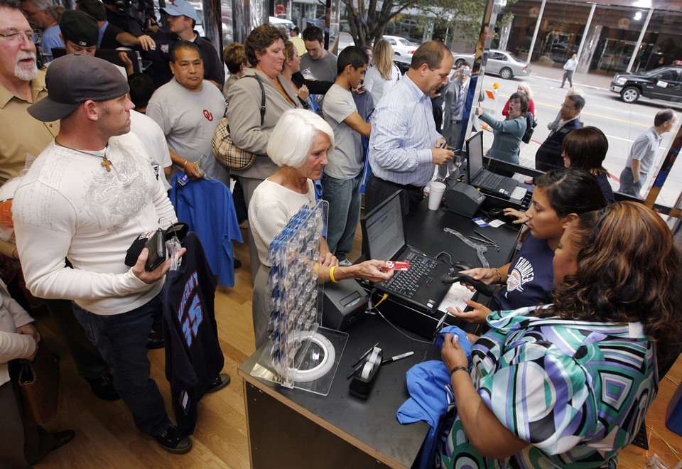 Photo - People stand in line to pay for OKC Thunder merchandise at the team store  after the unveiling of the Oklahoma City Thunder NBA team name at Leadership Square in downtown Oklahoma City, Wednesday, September 3, 2008. NATE BILLINGS, THE OKLAHOMAN