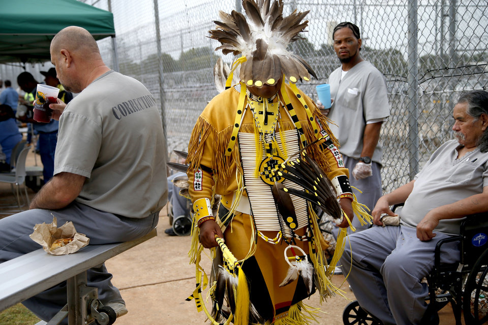 Photo - Inmate David Arkinson, a Sioux, walks past other inmates during the 27th Annual Confined Inter-Tribal Group Gourd Dance & Pow-Wow inside Joseph Harp Correctional Center in Lexington, Okla., on Friday, September 9, 2016. Photo by Bryan Terry, The Oklahoman