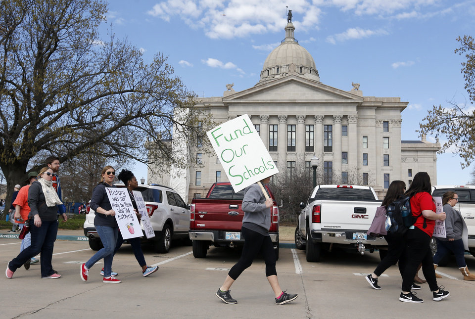 Photo - People march past the east side of the state Capitol during the eighth day of a walkout by Oklahoma teachers, in Oklahoma City, Monday, April 9, 2018. Photo by Nate Billings, The Oklahoman
