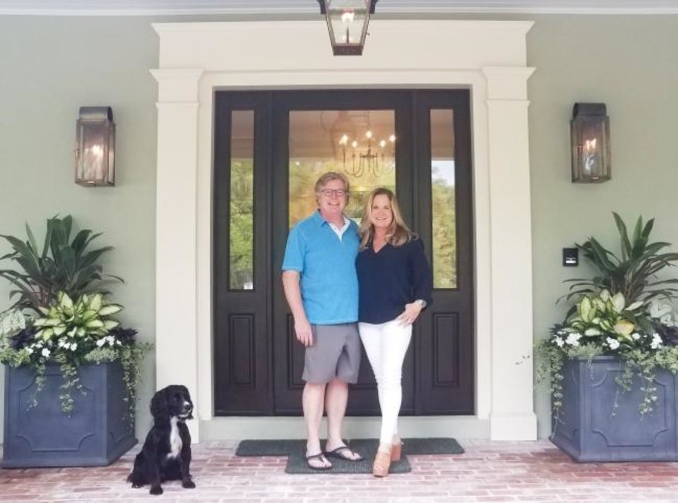 Photo -  Paula and Paul Loftus, and their field-bred English cocker spaniel Bracken, on the porch of their new right-size home. [MARNI JAMESON]