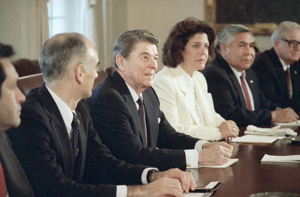 Photo - President Ronald Reagan, with Interior Secretary Donald Hodel at his side, meets on Monday, Dec. 12, 1988, in the White House Cabinet Room in Washington with Wilma Mankiller, principal chief of the Cherokee Nation and Leonard Burch, right, chairman of the Southern Ute Tribe.  AP ARCHIVE
