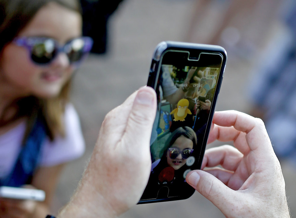 Photo - File: Michael Cross aims his phone at  Jane Stevens as they play Pokemon Go during a meetup for players of the game in Oklahoma City. [Photo by Bryan Terry, The Oklahoman archives]