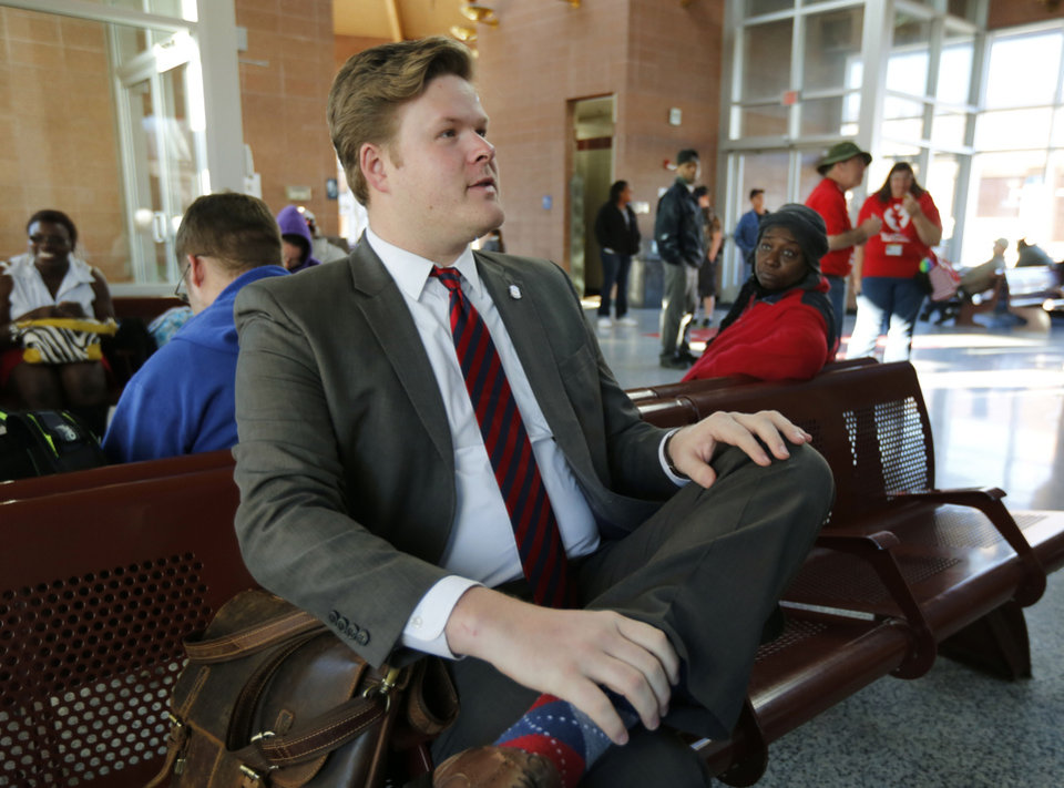 Photo -  Rep. Forrest Bennett speaks to bus riders recently as he waits for a bus to take him to the Capitol complex from Oklahoma City's Downtown Transit Hub. [Photo by Paul Hellstern, The Oklahoman]