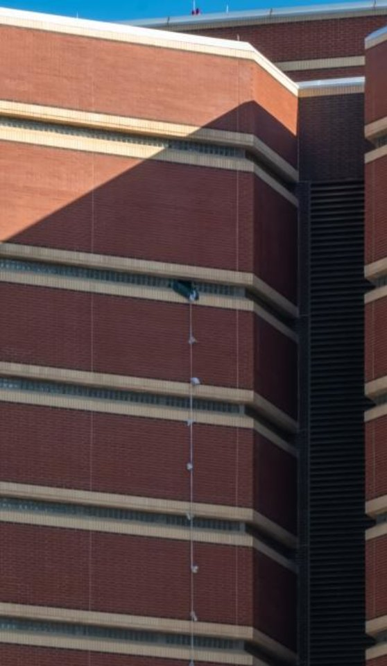Photo -  A rope made of bedsheets hangs from a broken window on the 12th floor of the Oklahoma County Jail, where two inmates escaped early Friday. [Dave Morris/The Oklahoman]