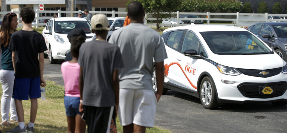 Photo -  People wait to take test drives and to ride in electric vehicles at OG&E's Electric Vehicle Ride and Drive event.