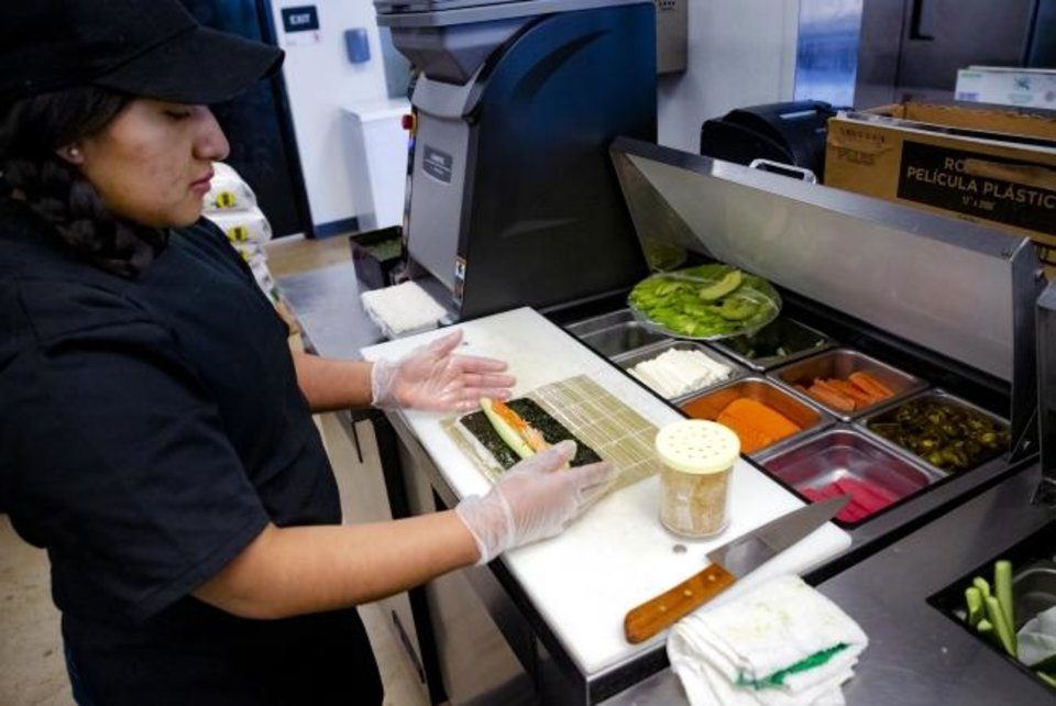 Photo -  Employee Julie Lopez makes a sushi roll at the new Nhinjo Sushi-Grill.  [Chris Landsberger/The Oklahoman]