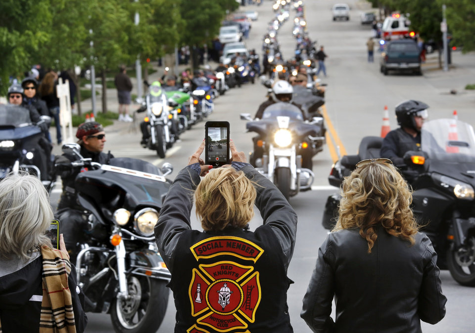 Photo -  People watch and take pictures Saturday as the procession of motorcycles continues along NW 5 Street. [Photo by Jim Beckel, The Oklahoman]