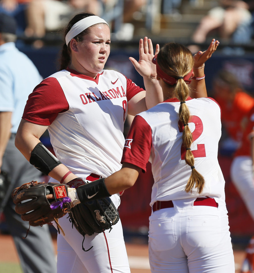 Photo - OU pitcher Paige Parker (8), left, high fives Sydney Romero (2) at the end of an inning during the championship game of the Big 12 softball tournament between Oklahoma and Oklahoma State (OSU) at ASA Hall of Fame Stadium in Oklahoma City, Saturday, May 13, 2017. OU won 2-0. Photo by Nate Billings, The Oklahoman