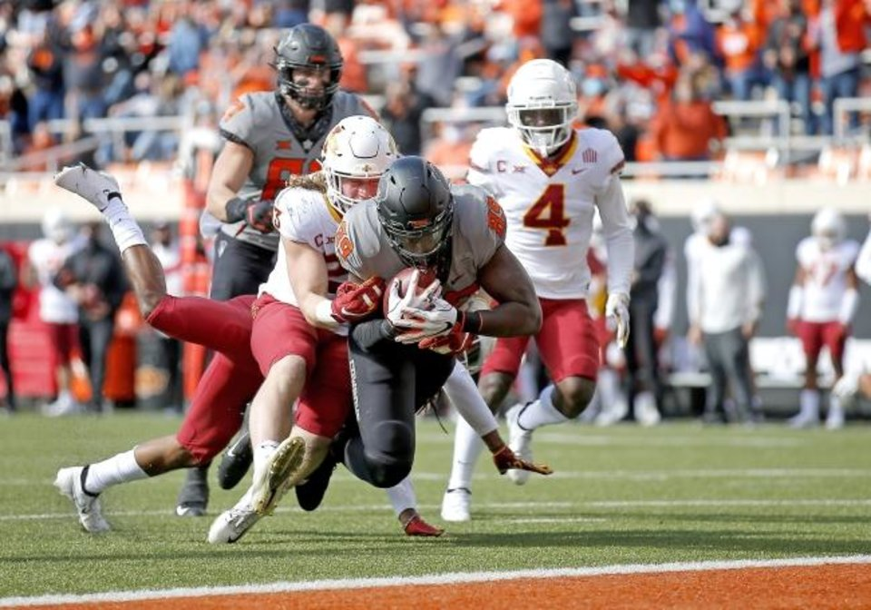 Photo -  Oct 24, 2020; Stillwater, Oklahoma, USA;   Oklahoma State Cowboys player Jelani Woods (89) scores a touchdown as Iowa State Cyclones player Mike Rose defends in the first quarter at Boone Pickens Stadium. Mandatory Credit: Sarah Phipps-USA TODAY Sports