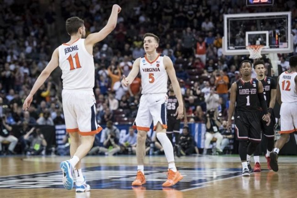 Photo -  Virginia guard Kyle Guy (5) and Ty Jerome (11) celebrate during a 71-56 win against Gardner-Webb on Friday. [AP Photo/Sean Rayford]