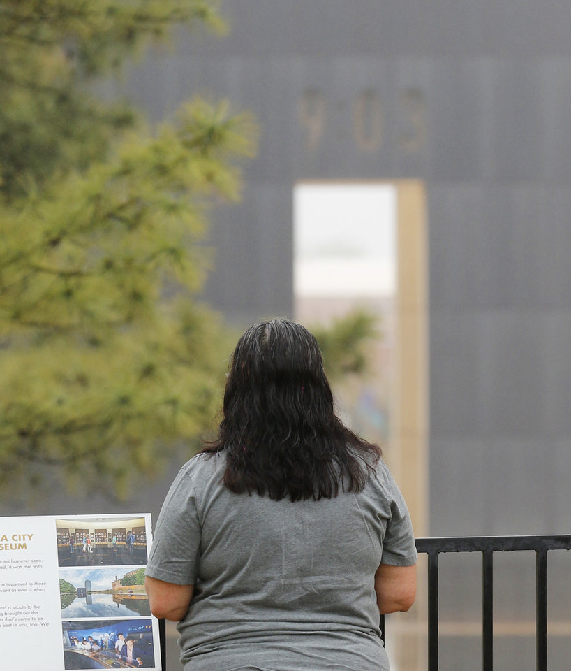 Photo - A woman pauses to look inside the Oklahoma City National Memorial and Museum on the 25th anniversary of the bombing of the Alfred P. Murrah Federal Building, in Oklahoma City, Sunday, April 19, 2020. The memorial remains closed and did not hold a live remembrance ceremony because of the coronavirus pandemic. [Doug Hoke/The Oklahoman]