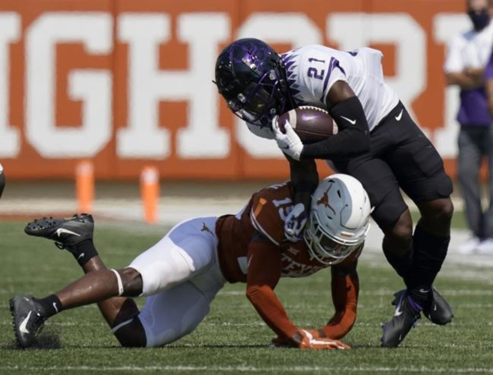 Photo -  TCU running back Daimarqua Foster (21) is hit by Texas defensive back Chris Brown (15) on a run during the first half Saturday in Austin, Texas. [AP Photo/Eric Gay]
