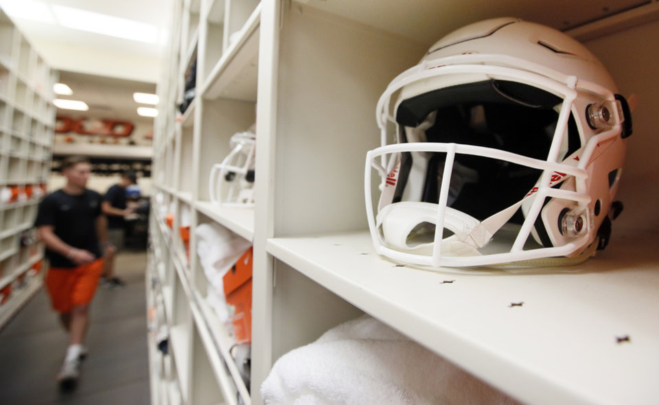 Photo -  A white helmet — an OSU standard for years — sits on a shelf in the football equipment area at Boone Pickens Stadium in Stillwater. [PHOTO BY NATE BILLINGS, THE OKLAHOMAN]
