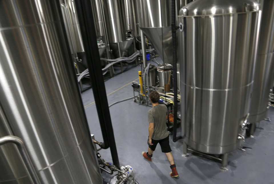Photo -  Brewer Will Quinlin works to move batches of ale to be fermented last year at Coop Ale Works. [Photo by Sarah Phipps, The Oklahoman Archives]