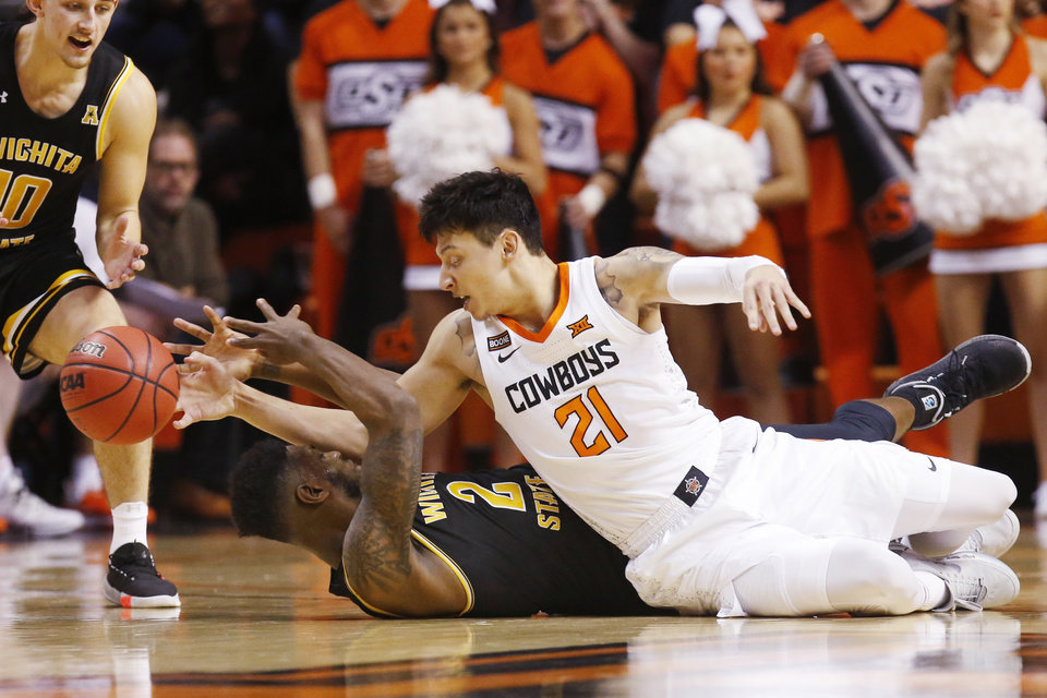 Photo - Oklahoma State guard Lindy Waters III (21) knocks the ball away from Wichita State guard Jamarius Burton (2) in the second half of an NCAA college basketball game in Stillwater, Okla., Sunday, Dec. 8, 2019. (AP Photo/Sue Ogrocki)