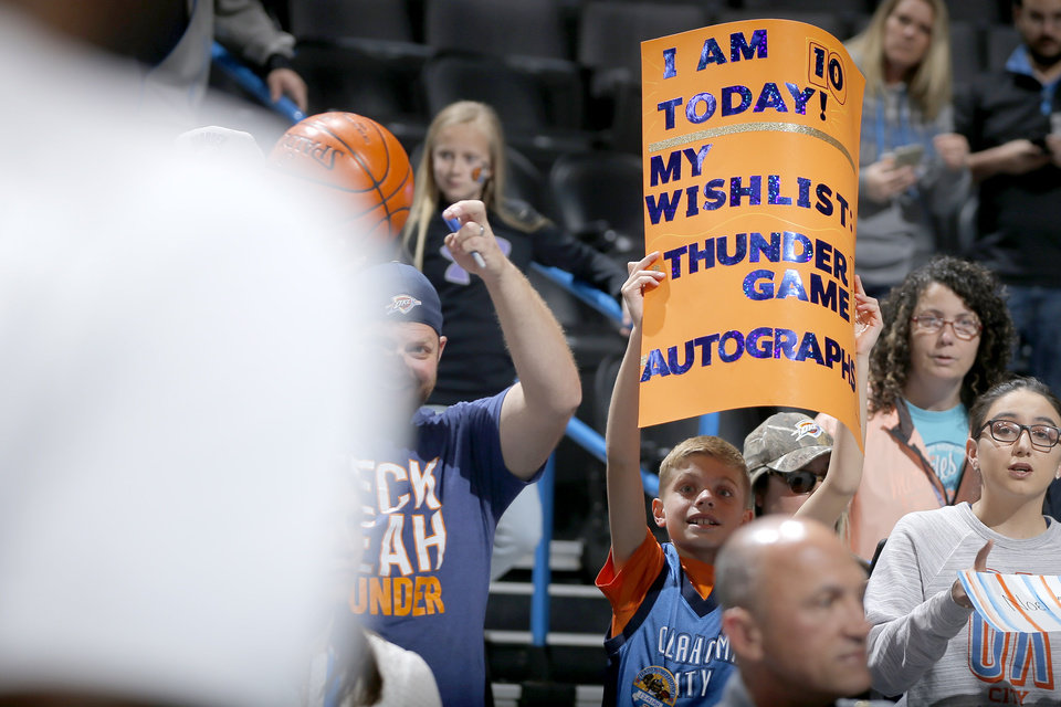 Photo - Izaiah Jennings, 10, and his dad Broc Jennings, from Yukon, Okla., try to get an autograph before an NBA basketball game between the Oklahoma City Thunder and the Sacramento Kings at Chesapeake Energy Arena in Oklahoma City, Sunday, Oct. 21, 2018. Photo by Bryan Terry, The Oklahoman