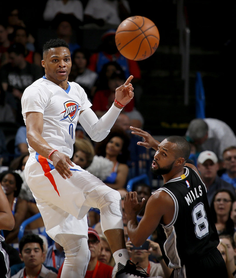 Photo - Oklahoma City's Russell Westbrook (0) passes the ball over San Antonio's Patty Mills (8) during an NBA basketball game between the Oklahoma City Thunder and the San Antonio Spurs at Chesapeake Energy Arena in Oklahoma City, Saturday, March 26, 2016. Photo by Bryan Terry, The Oklahoman