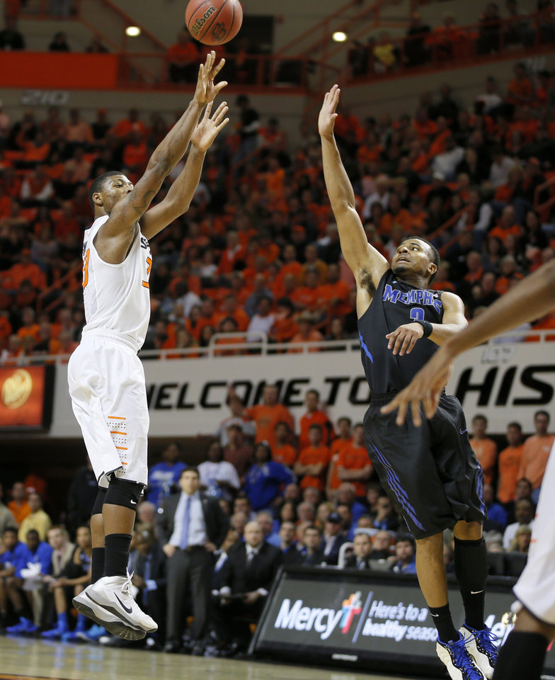 Photo - Oklahoma State's Marcus Smart (33) puts up a shot beside Memphis' Chris Crawford (3) during an NCAA college basketball game between Oklahoma State and Memphis at Gallagher-Iba Arena in Stillwater, Okla., Tuesday, Nov. 19, 2013. Photo by Bryan Terry, The Oklahoman