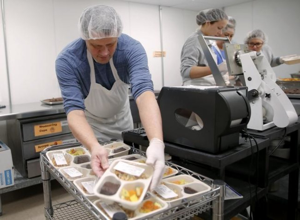 Photo -  Dennis Wallis helps package meals for delivery at Edmond Mobile Meals. [Bryan Terry/The Oklahoman]