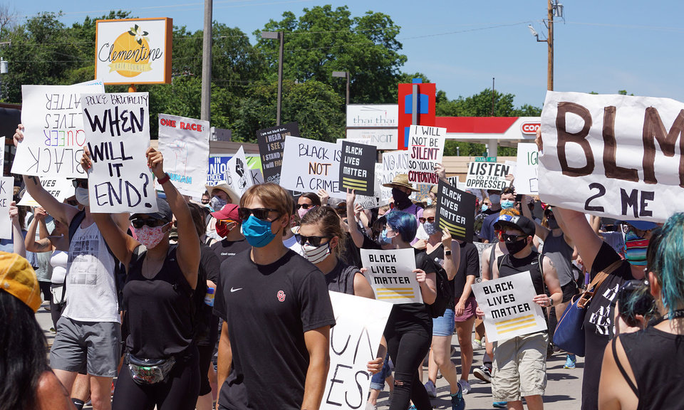 Photo - Protestors march down Main Street from the east parking lot of Norman High School during the George Floyd protest on Saturday, June 6, 2020, in Norman, Okla. [Ellie Melero/The Oklahoman]