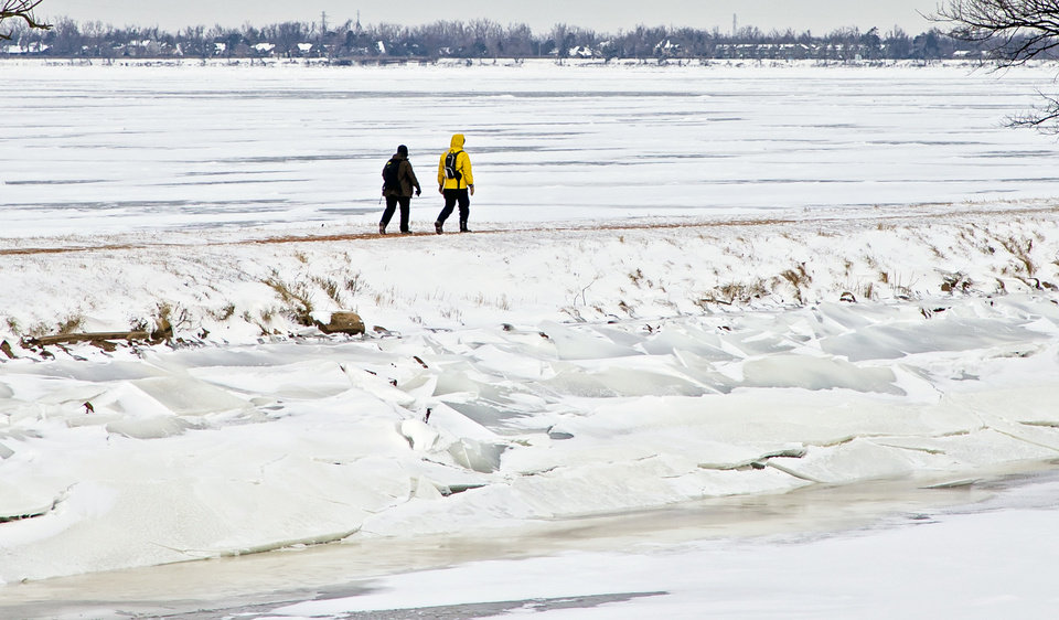 Photo - A couple walk along the icy shoreline at Lake Overholser in Oklahoma City, Okla. on Tuesday, Feb. 16, 2021.  [Chris Landsberger/The Oklahoman]