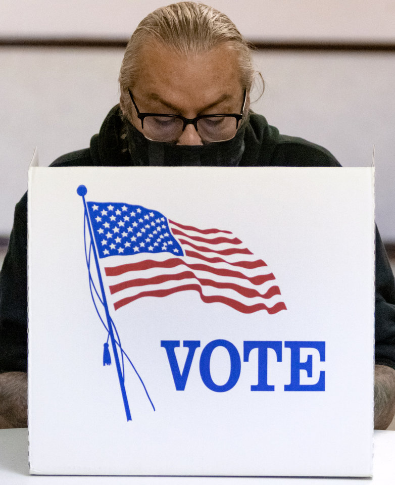 Photo - A voter fills out his ballot at the Shields Boulevard Baptist Church in Oklahoma City, Okla. on Tuesday, Nov. 3, 2020. [Chris Landsberger/The Oklahoman]