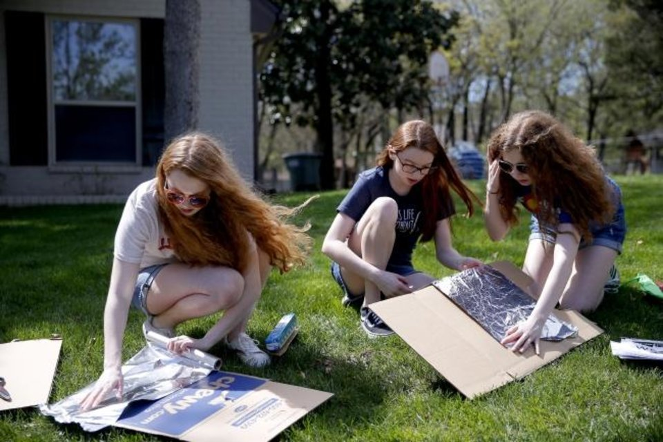 Photo -  Sisters McKenna Cash, 19, Lorelei Cash, 14, and Tierney Cash, 17, assemble a scene for a drive-thru Stations of the Cross outside their Edmond home. [Bryan Terry/The Oklahoman]